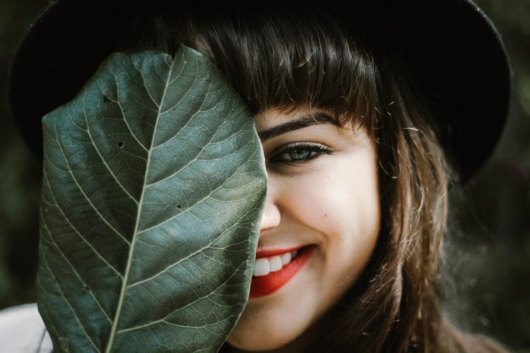 Girl Smiling Behind Leaf